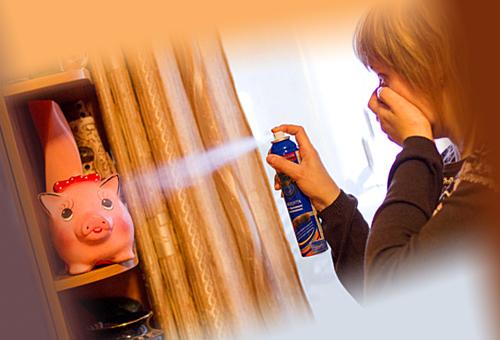 Девушка распыляет средство от блох в квартире